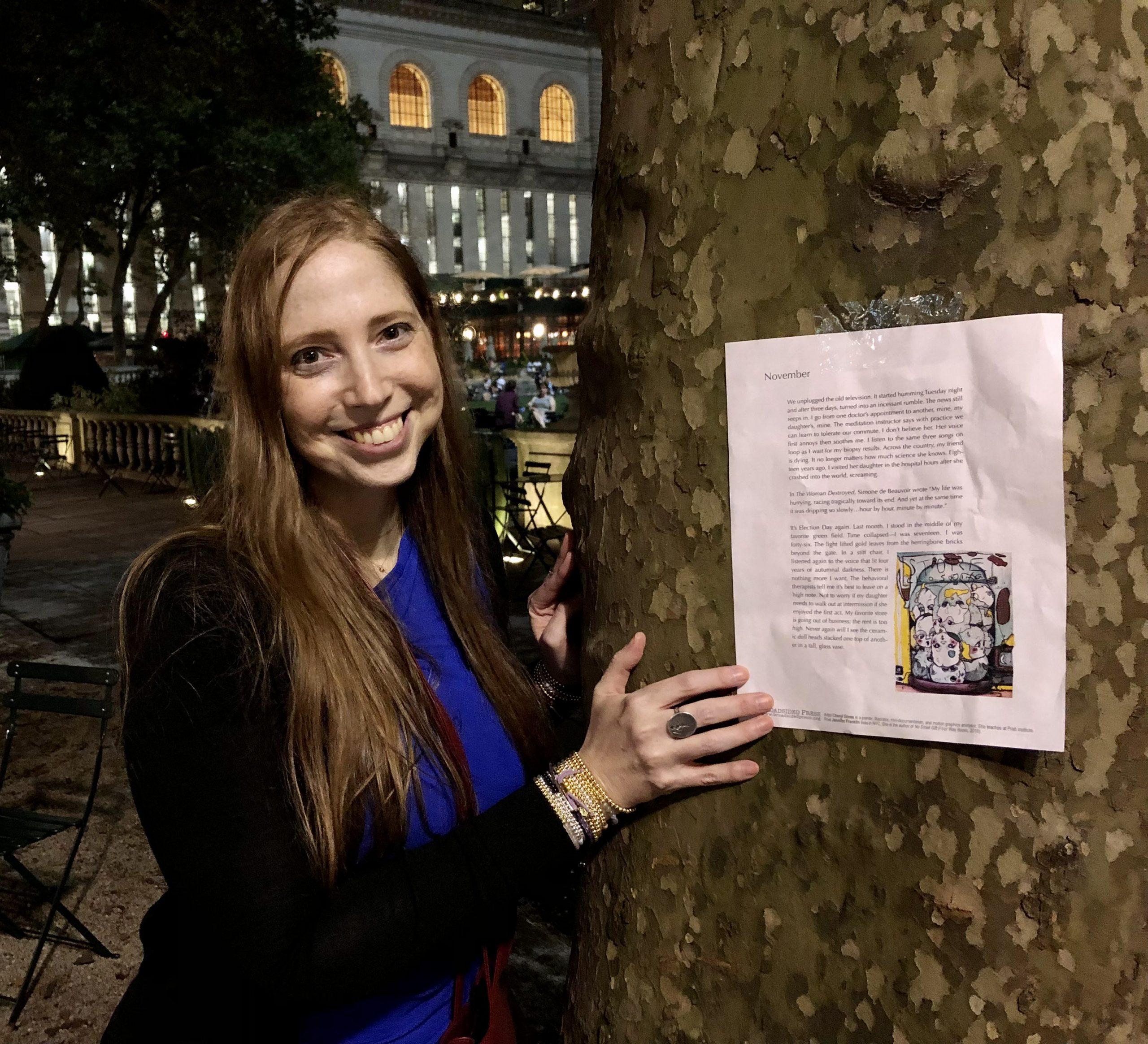Poet Jennifer Franklin smiling left in evening next to broadside on tree.