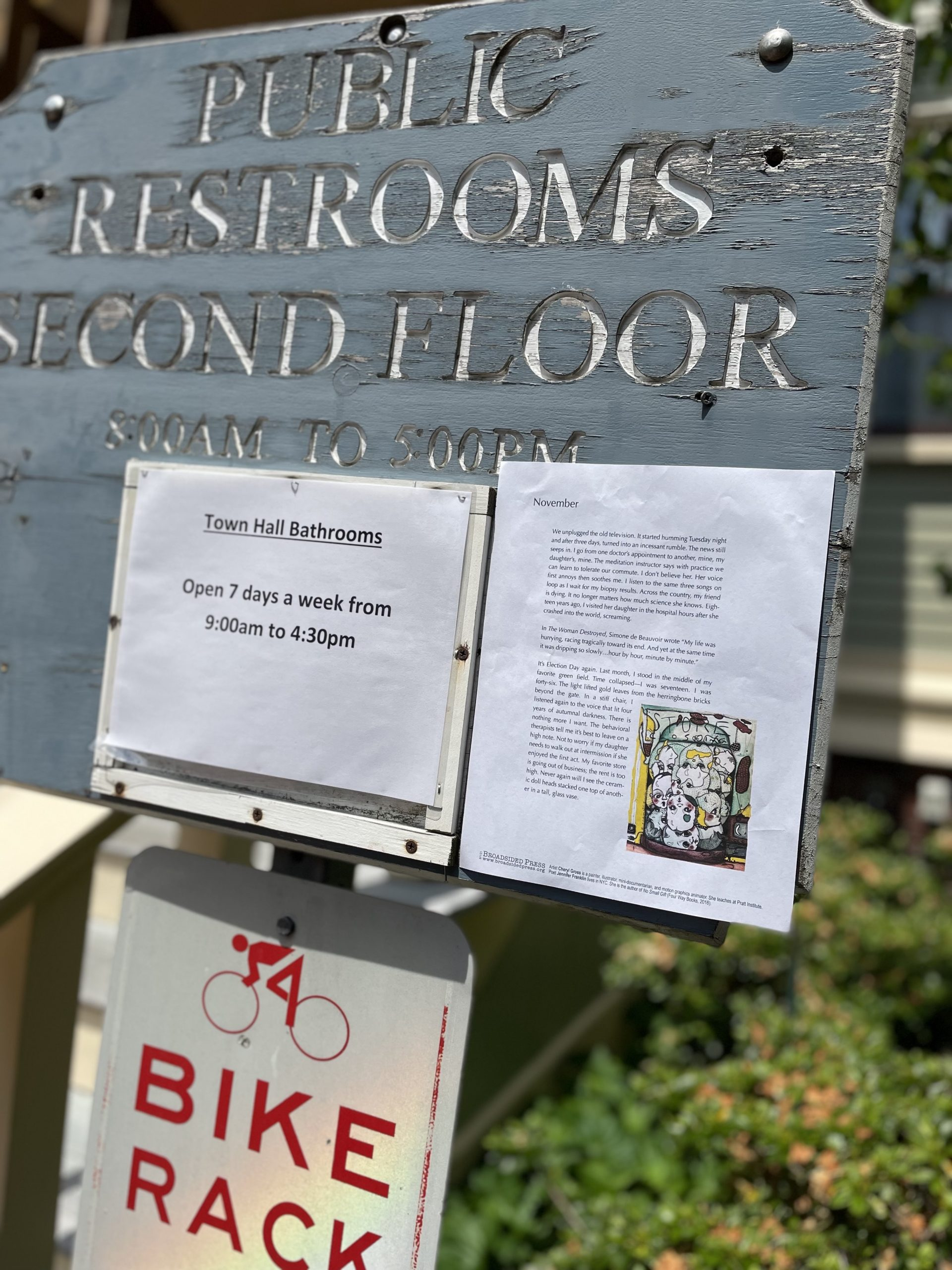 """Grey wooden sign reads """"Public Restrooms Second Floor"""" with bike rack sign below and broadside taped to right bottom corner of wooden sign."""
