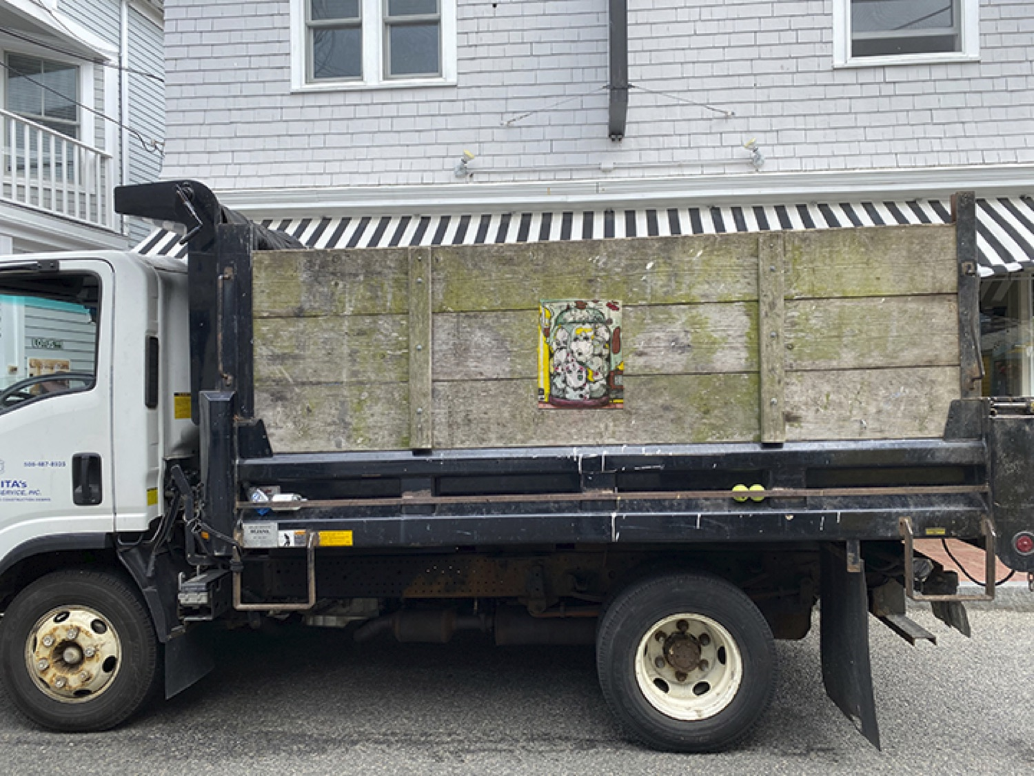 Broadside center on wooden side of large truck in front of white building, photo as mid-long shot.