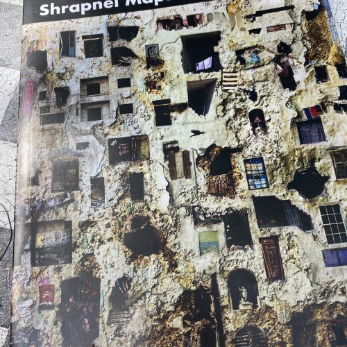the cover of Shrapnel Maps, book of poems by Philip Metres. Some cracked, tiled floor in the background.