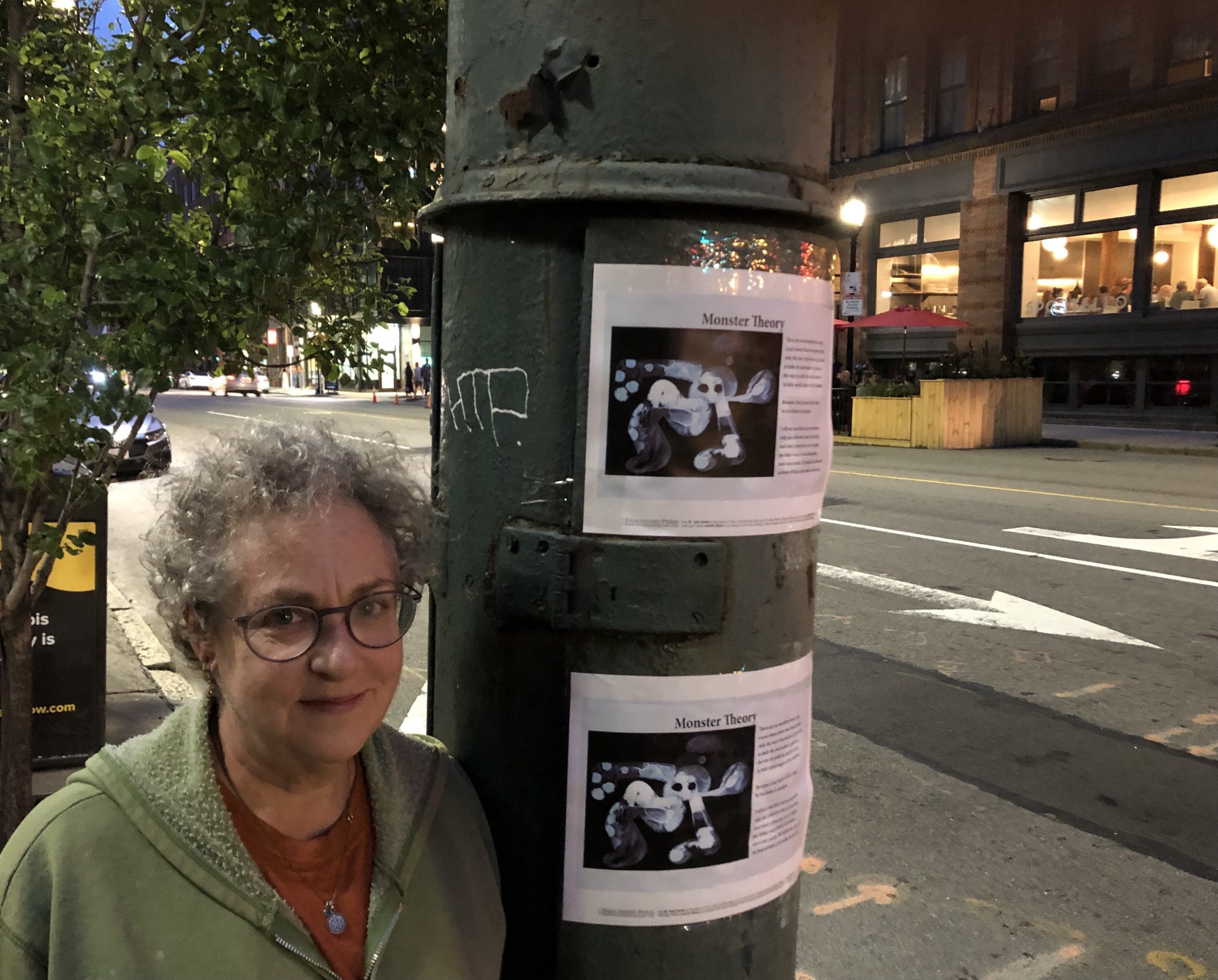 The artist stands left of the two copies of her broadside posted in vertical row on an electric pole.