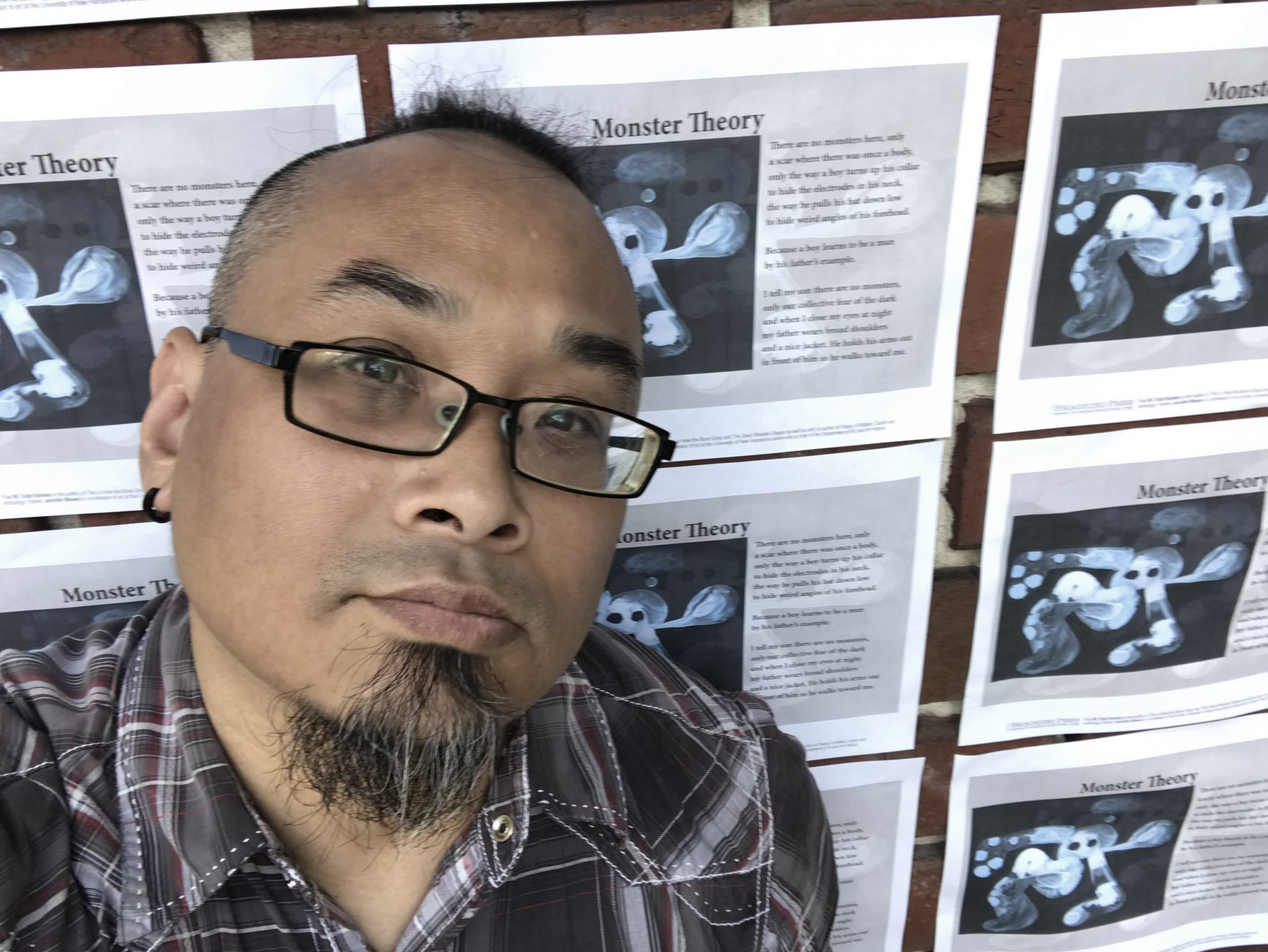 The poet stands in front of more than nine copies of his broadside positioned in a grid.